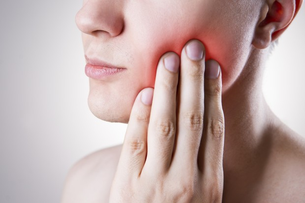 A woman is holding her cheek due to a toothache. Sensitive teeth can cause problems like this.