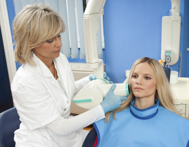 A dentist uses an X-ray machine to examine a patient's mouth. The patient is wearing a lead apron to protect herself from radiation exposure.