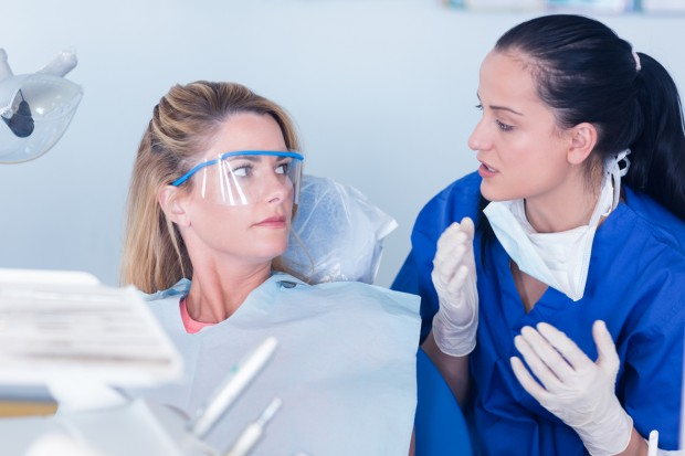A dentist is discussing with her patient the risk of a procedure recommended by the patient's dental insurance.