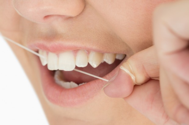 A close up of mouth and dental floss in a white background.
