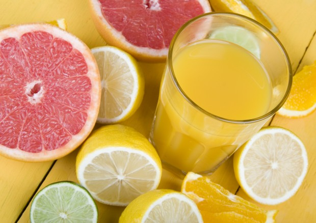A table with various fruits, including lemons, which can cause tooth enamel damage.