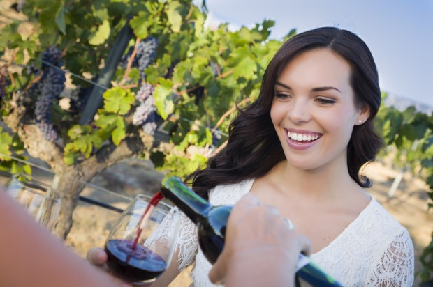 A young adult woman enjoying a glass of wine in the vineyard with friends.