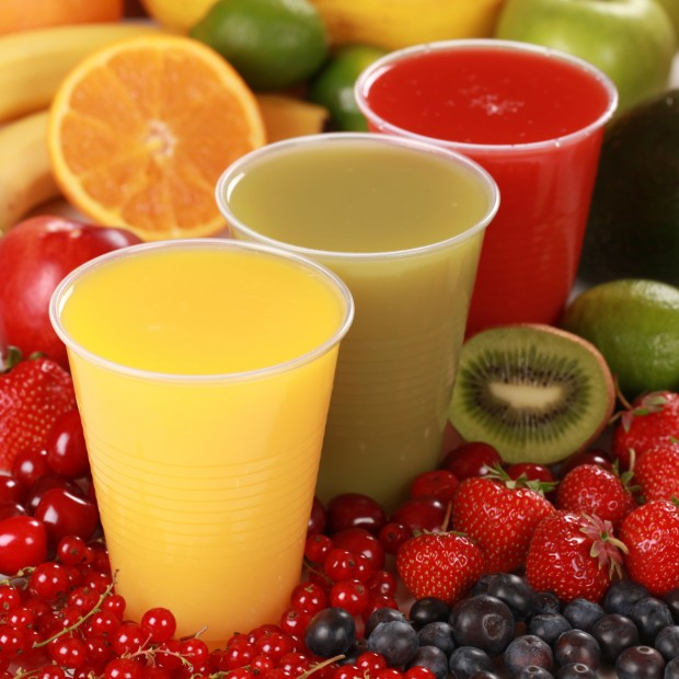 Cups with different kinds of fruit juices surrounded by fresh fruits.