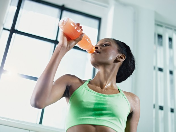 A young woman dressed in sportswear, is sweating and drinking a sports drink, which can cause tooth erosion.