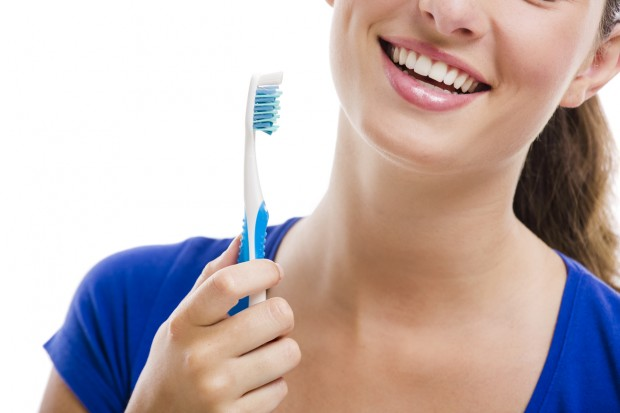 A beautiful woman holding a toothbrush, smiling and showing the top gum of her mouth.