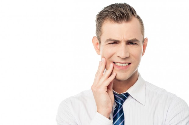 A businessman with a toothache from gum disease.