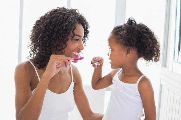 A mother and daughter showing off the proper techniques for brushing your teeth.