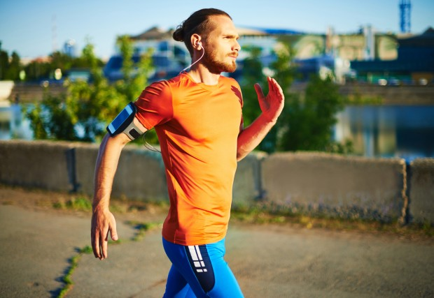 Portrait of young attractive sportsman running outside.