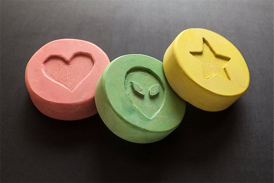 Three ecstasy pills of varying color on a black backgroudn.